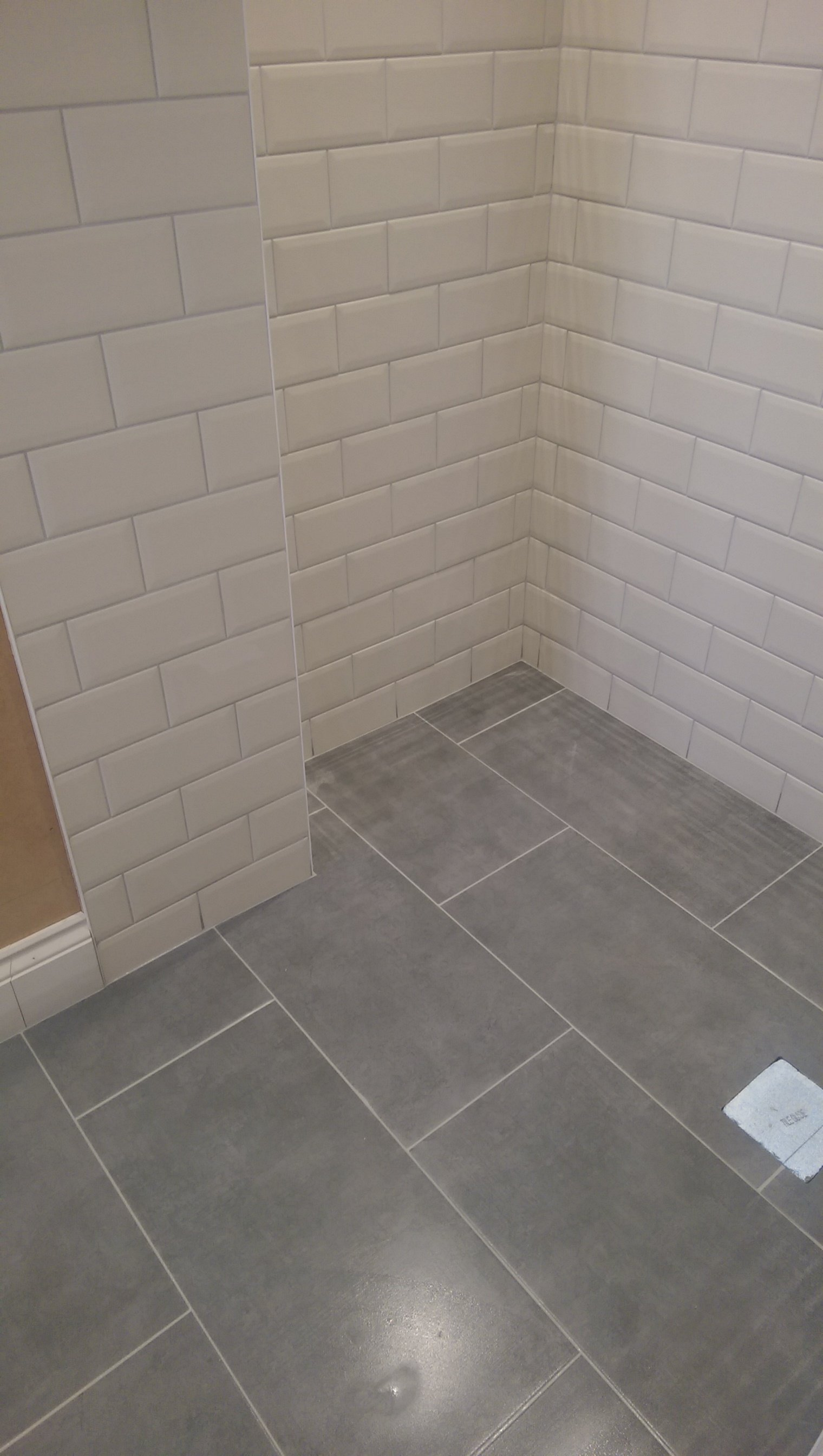 Gray floor tiles and white wall tiles in a new bathroom installation